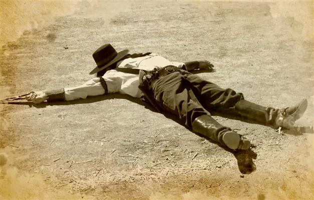 Dead gunfighter laying in street