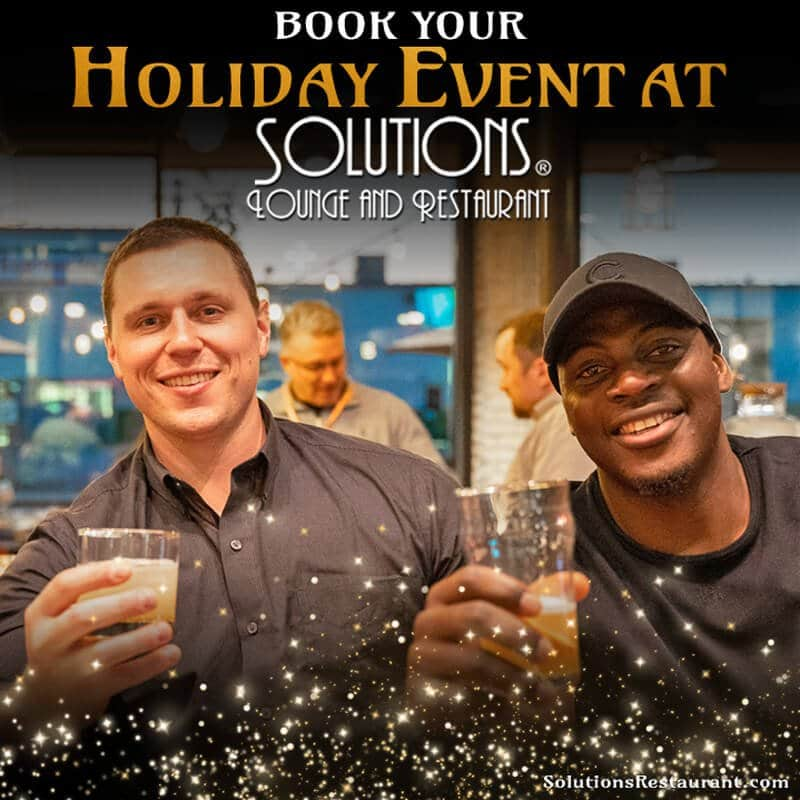 Two men toasting at the Solutions Lounge bar